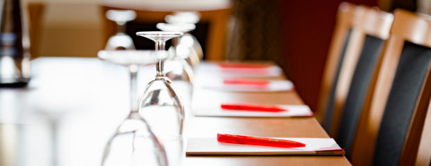 Image of table set up with notepads, glasses and water